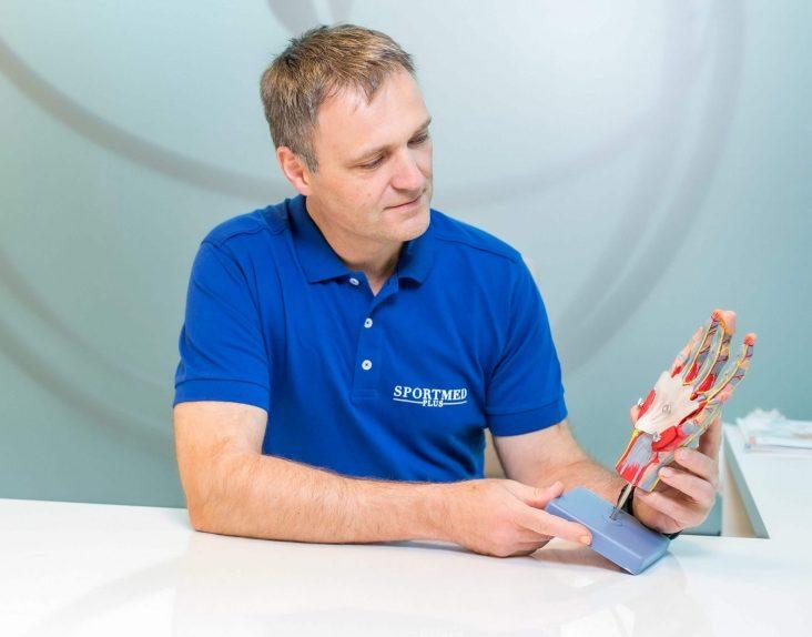 Sportmed-Plus-Arzt Dr. Christian Windhofer erklärt anhand eines Modells die neuen Behandlungsmöglichkeiten bei Handverletzungender Hand